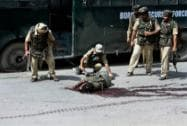 Paramilitary soldiers stand near the dead body of a terrorist