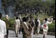 Pakistani protesters chase a troop of riot police officers during a protest near prime minister's home in Islamabad