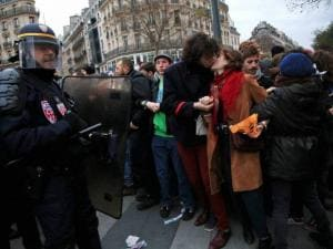 A couple facing riot police officers kiss