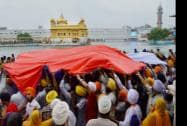 Devotees protecting the palanquin installed with Guru Granth Sahib from rain