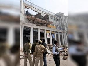 Police investigate near the site of the collapsed section of a building in C-Block area of Connaught Place