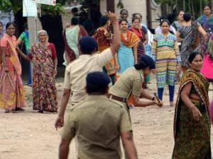 A woman cop charges a woman during a clash in Jamnagar