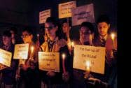 Holding  candles in their hand and placard School children