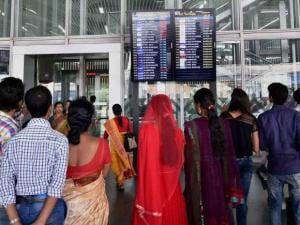 Air passengers look at a flight information display board at NSCBI Airport in Kolkata