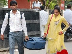 Passengers carry their luggage as buses