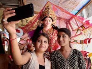 Girls clicking selfie with Goddess Durga idol on the occasion of Durga Puja Festival