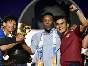 Brazilian football legend Pele presents the winning trophy to AIFF team