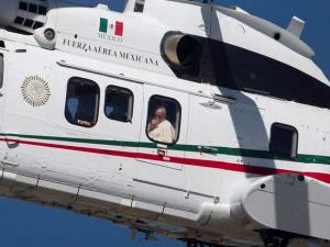 Pope Francis peers from the window of his helicopter as he arrives in San Cristobal de las Casas, Mexico
