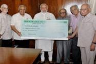 Prime Minister Narendra Modi being presented with a cheque for the PMNRF by Punam Suri,  President, DAV College Managing Committee