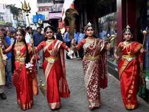 Girls dressed up as Goddess Durga walk through a street, ahead of Durga Puja festival