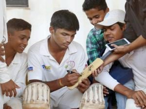 Pranav Dhanavade signs autograph for a fan after creating a world record by scoring 1009 runs