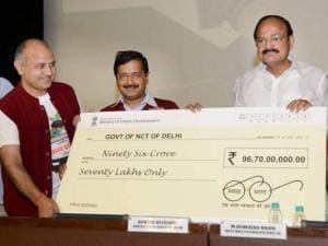 Union Urban Development Minister M Venkaiah Naidu hands over a cheque to Delhi Chief Minister Arvind Kejriwal