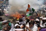Delhi Pradesh Congress Committee (DPCC) activists burn effigies of Prime Minister Narendra Modi and Delhi Chief Minister Arvind Kejriwal during a protest at Jantar Mantar
