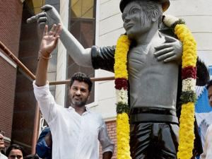 Actor-Director Prabhu Deva strikes a pose with Michael Jackson statue after unveiling it at a private university in Chennai .