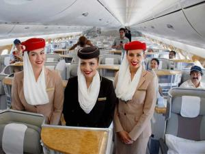 Airhostesses pose inside a Emirates A380  aircraft which is parked for static display at the India Aviation 2016 at Begumpet Airport in Hyderabad