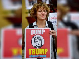An activist holds a placard during a protest against the newly sworn-in US President Donald Trump in Bengaluru