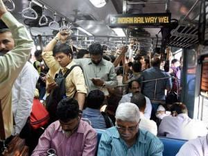 Commuters travel in a suburban local train of Western Railway on the eve of the Railway Budget in Mumbai