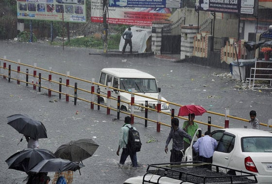 People wade at a flooded road amid heavy rains in Haridwar on Monday.