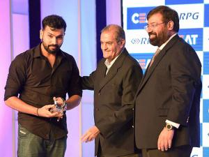 Industrialist Harsh Goenka and former Indian cricketer Nari Contractor present the CEAT Cricket Rating Indian Cricketer of the year award to cricketer Rohit Sharma in Mumbai