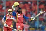 Royal Challengers Bangalore Chris Gayle raises his bat after competing his 100 runs