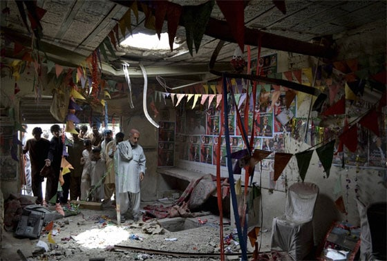 Pakistanis check damages at an election campaign office of Pakistan People's Party, PPP, destroyed by a bomb blast in Quetta