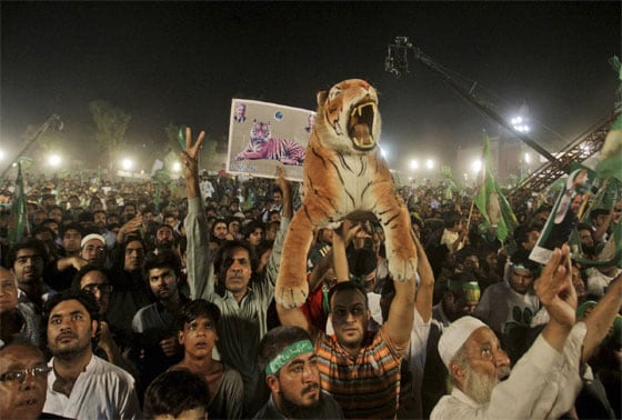 Supporters of Pakistan's former Prime Minister Nawaz Sharif, listen to him delivering a speech, during an election campaign rally, in Lahore