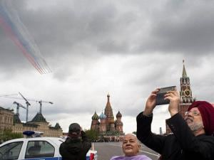 Tourists take pictures with cell phones while Russian fighter jets leave a smoke trail in the colors of the state flag, as they fly over the St. Basil's Cathedral, center, and the Spasskaya