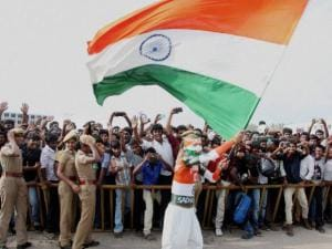 A fan waves a Tricolour during the Isha Gramotsav, a rural revitalization programme