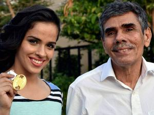 Badminton player Saina Nehwal with her father Harvir Singh shows medal which she won in second Australian Open title after defeating China's Sun Yu, in Hyderabad