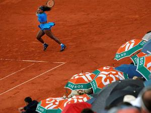 Spectators shield themselves from the rain as Serena Williams of the U.S. returns in the third round match of the French Open tennis tournament against France's Kristina Mladenovic at the Rola