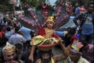 A Bangladeshi Hindu devotee carries on his head, a child dressed like Hindu god Krishna in a basket