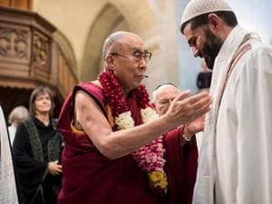 Tibetan spiritual leader the Dalai Lama, Tenzin Gyatso, speaks to a man during the Peace prayer at the Grossmuenster church in Zurich