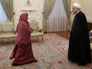 Iranian President Hassan Rouhani, right, welcomes Indian Foreign Minister Sushma Swaraj at the start of their_meeting in Tehran, Iran