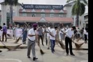 Employees of NF Railwaya sweep a road as part of Swachh Bharat Abhiyan