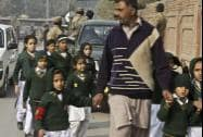 A plainclothes security officer escorts students evacuated from a school