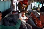 Pakistani rescue workers take out students from an ambulance