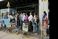 Passengers wait in long queues at a prepaid taxi booth