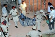 Punjab police personnel carry the body