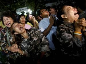 Thai people cry after Royal Palace's announcement outside Siriraj Hospital where the king is being treated