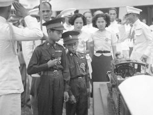 thirteen-year-old King Ananda of Thailand, left, and his brother Prince Bhumibol, right, inspect a model train presented to him
