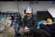 A Nepalese man sits near earthquake injured children at a hospital, in Kathmandu