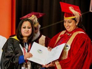 Union Minister of HRD Smriti Irani falicitates a student
