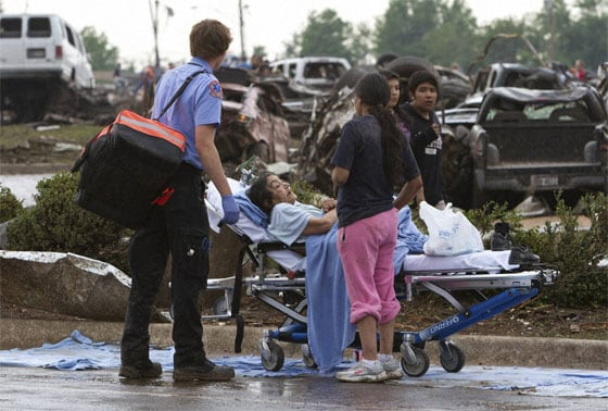 A Moore Medical Center patient sits in the parking lot after a tornado damaged the hospital in Moore, Oklahoma