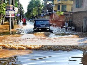 A vehicle wades through one of the water-logged streets of Anil Nagar after heavy showers in Guwahati