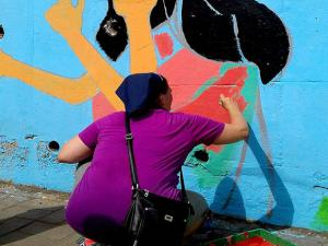 Amanda, an American deaf trainer, works on a mural themed on sign language painted on the wall of a flyover