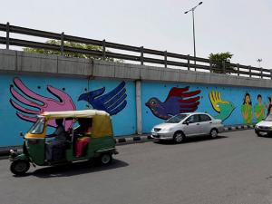 Vehicles move past a mural painted by a group of deaf persons