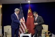 US Secretary of State John Kerry reaches to shake hands with China's Foreign Minister Wang Yi
