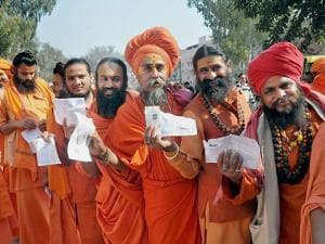 Saints of Juna Akhara stand in line to cast their vote during Uttarakhand assembly election