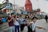 A group of Japanese tourists enjoy the sights and sounds at Dashashwamedh Ghat in Varanasi on Sunday