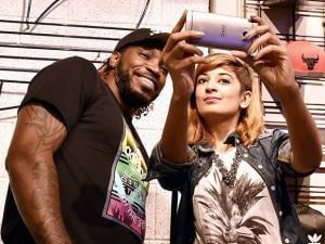 A Girl takes a selfie with RCB player Chris Gayle during an event at a mall in Bengaluru